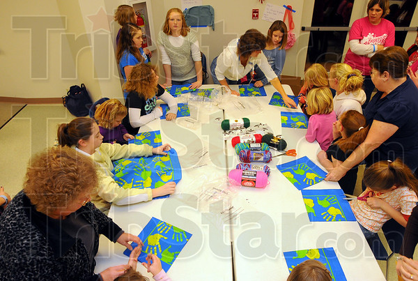 Hands on: Girl scouts and parents create crafts as part of the cookie sales kick-off night at Girl Scout headquarters.