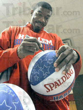 Signing: Buckets Blake of the Harlem Globetrotters signs a basketball he's about to give to a local family at the Salvation Army Friday afternoon.