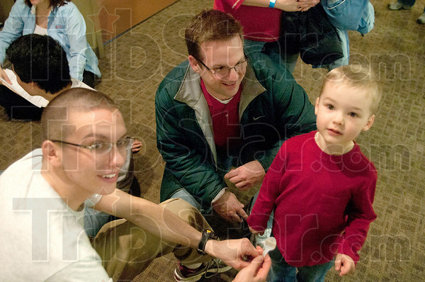 Lift Off: Eric Louk, top middle, watches as son Owen, right, launches a marshmallow with help from Rose-Hulman student Todd Grigsby. The three were at the Children's Science and Technology Museum on science saturday learning about the transfer of energy, angle measurement and inertia.