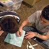 Blueprints: Six year old Omar Abuhamdieh explains his design for a marshmallow catapult to Rose-Hulman student Christopher Hakoda.