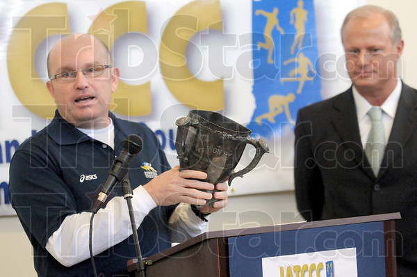 Donation: Terry Lakes of Marion High School donates a track and field cup from the early 1900's. Dave Patterson (R) of the Convention and Visitor's Bureau accepted the cup.