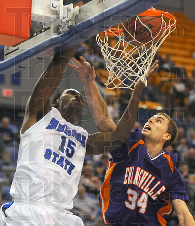 And 1: Evansville's Denver Holmes fouls Carl Richard as he dunks the ball following a steal.