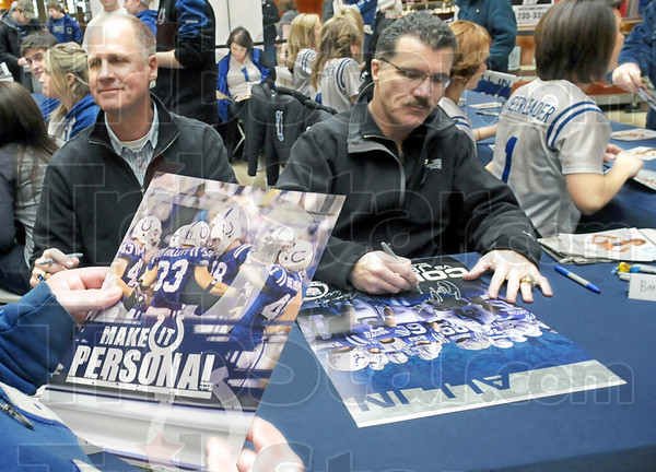 Autographs: Former Colts players Mark Herrmann (L) and Barry Krauss sign autographs at Honey Creek Square Wednesday morning.