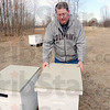 Bee mine: Local bee keeper Steve Hiatt puts the top back on a hive after checking for activity Wednesday afternoon.