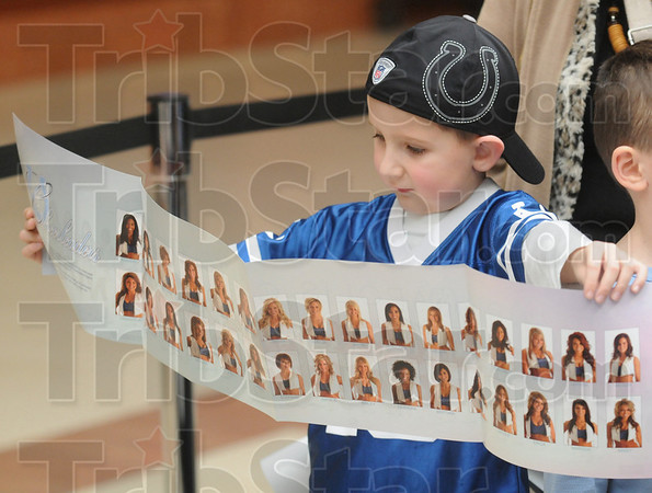 Fan: Five-year-old Logan Young of Terre Haute looks at a Colts cheerleader fold-out as he visits Honey Creek Square Wednesday morning.