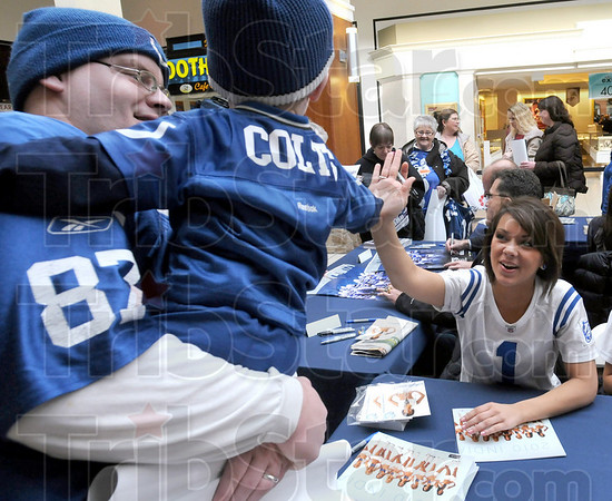 """High five: Two-year-old Erick Standley Jr. gets a """"high five"""" in the arms of his father Erick Sr. from an Indianapolis Colts cheerleader Wednesday morning."""