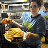 Mel's: Mel's Diner waitress Stacy Mullins prepares to take lunch to customers Tuesday afternoon. Cooks Brian Oxendine, Jason Wood and Scott Morgan prepare foods in the background.