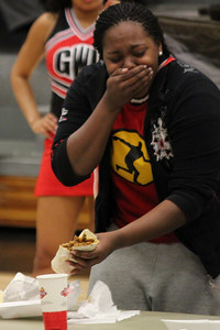 One of the participants struggles to eat a burrito as part of the halftime fun and games at the women's basketball game on January 31, 2011.