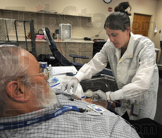 Tribune-Star/Jim Avelis<br /> Giving: Terre Haute Regional Hospital employee Ronald Austin gives a pint of blood in the Fallen Officers Blood Drive Thursday afternoon. Blood Tech Kylee Wood draws the blood.