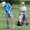 Jr. action: George Hosking hits as shot during Jr. City Championship action Thursday afternoon. Watching the play is the tournament's youngest player David Hayes.