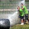 Splash attack: A team of Jr. Fire Academy participants attack the barrel with a hose during Thursday's events from the school.