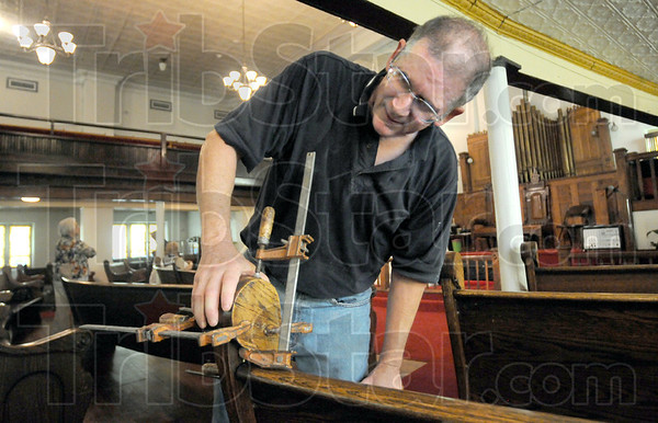 Pew restoration: Andy McAleese adjusts a clamp on a pew in the Allen Chapel Thursday afternoon. He's doing the work restoring the chapel pews.