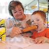 Tribune-Star/Rachel Keyes<br /> Fair food: Grandmother Lois Mathes holds a corn dog at grandson Mason Mills takes a big bit.