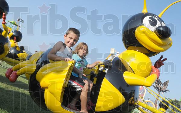 Tribune-Star/Rachel Keyes<br /> Bubble bee: R.J. Mattas and sister Ella Mattas ride the bumble bee at the Vigo County Fair Sunday.