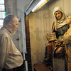 Tribune-Star/Rachel Keyes<br /> In service: Usher Michael Cummins stands looking at a statue of St. Ann early Sunday morning as he waits to great parishioners.