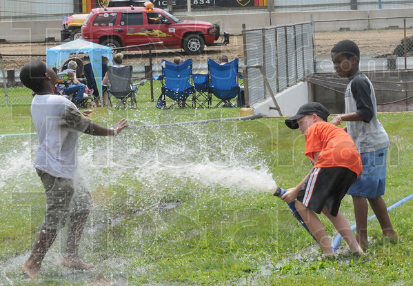 Tribune-Star/Rachel Keyes<br /> Waterworks: Devante Payne (left) Kyle Wolf (middle) and Tyren Payne (right) play in the water as crews pump the flooded tunnel at the Terre Haute Action Track Sunday.