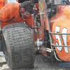 Tribune-Star/Rachel Keyes<br /> New set of wheels: George Gamester changes out the tires on brother Russ Gamester's car in action Sunday at the Terre Haute Action Track.