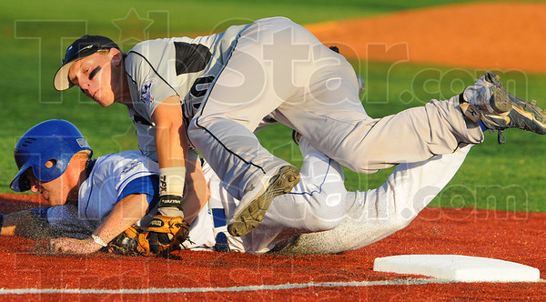 Tribune-Star/Jim Avelis<br /> Rough & tumble: Rex baserunner Lucas Hileman upends Lorain County third baseman Zac Blair attempting to reach the bag. Hileman was out on the play.