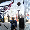 Volunteers: Indiana State University football players Ronnie Fouch and Justin Wood shoot free throws as they man the game for the annual St. Benedict's Festival Friday evening.
