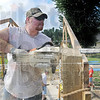 Tribune-Star/Rachel Keyes<br /> Raise your saw: Jeremy Montgomery levels off part of the shelter with his chain saw before the roof goes up.