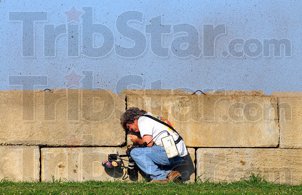 Tribune-Star/Jim Avelis<br /> Dirt track: Professional photographer Chris Peterson ducks as a sheet of mud rises up and over the wall as passing race car speeds by.