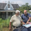 Abandoned house: Vigo County officials Dave Reeves and Dale Sowards review paperwork regarding the abandoned home at 7951 S. State Road 63 Wednesday afternoon.