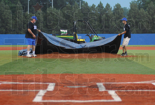 Tribune-Star/Rachel Keyes<br /> Cover up: The grounds crew at the Rex cover up the mound during a rain delay Saturday evening.