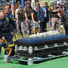 Tribune-Star/Jim Avelis<br /> Partner: Terre Haute police Sgt. Terry John escorts Shadow past Brent Long's casket at Mt. Pleaasant Cemetery.