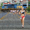Railroaded racers: Eventual race winner Cassie Hunt of Crawfordsville, Indiana leads the field down Wabash Avenue as a CSX train splits the women's Mayor's Cup Mile Monday morning.