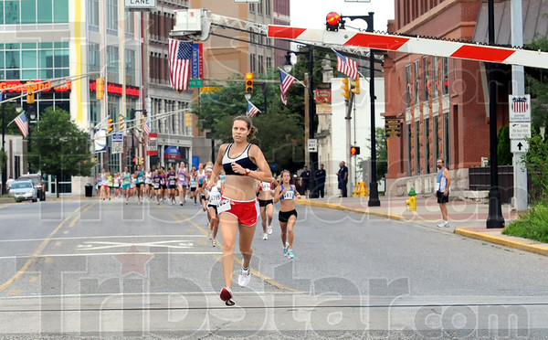 Race: Cassie Hunt eyes the railroad crossing arm as it comes down during the women's Mayor's Cup mile Monday morning.