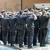 Salute: Scores of police officers salute as the body of fallen officer Brent Long arrives at Union Hospital Tuesday afternoon.