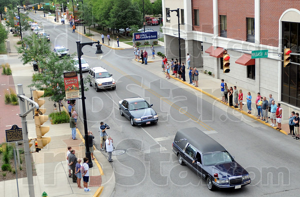 Respectful: A long line of police vehicles follows the hearse carrying the body of Terre Haute police officer Brent Long along 7th street as they travel to the Mattox-Ryan Funeral Home Tuesday evening.