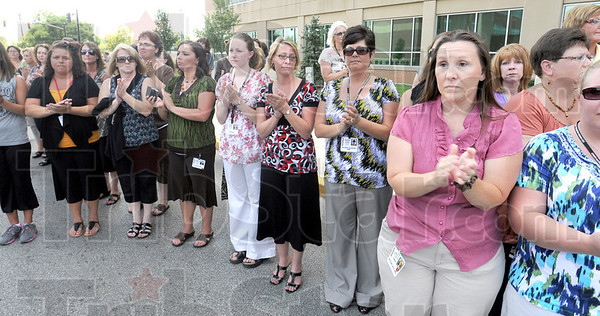 Spontaneous: Bystanders break out in spontaneous applause as the motorcade carrying the body of Terre Haute police officer Brent Long arrives at Union Hospital Tuesday afternoon.