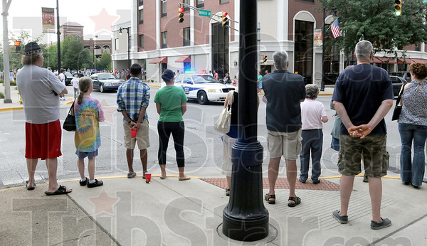 Silent: Spectators stand silently at the corner of 7th and Wabash as the motorcade escorting the body of fallen police officer Brent Long Tuesday evening.