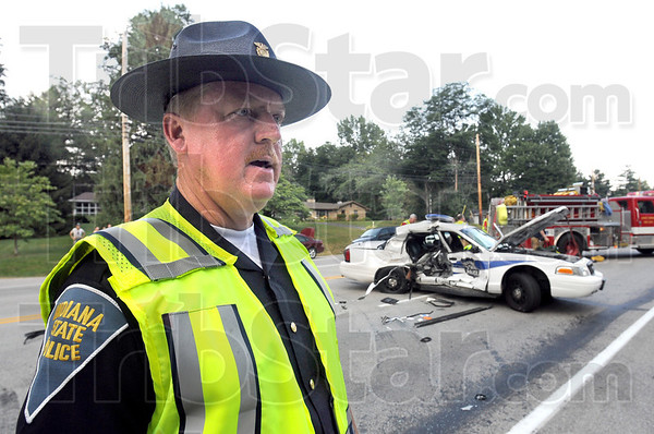 Information: Indiana State Police public information officer, Sgt. Joe Watts gives available information to Tribune-Star reporter Arthur Foulkes at the scene of Tuesday's crash involving a police unit.