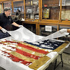 Historic find: Sullivan County Historic Museum workers Tom Frew and Rose Gates carefully uncover the remains of a Civil War Flag recently found at the museum.