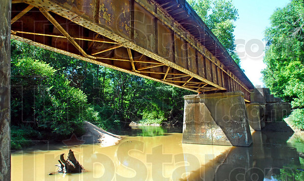 Dangerous waters: Water flows under the CSX railroad tressel Tuesday morning. The tressel was the scene of an accident involving a train crossing the structure Sunday.