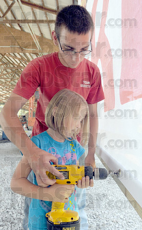 Tribune-Star/Jim Avelis<br /> Fair time: Wabash Valley Fairgrounds emloyee Brandon Scarbrough helps Hannah Keith secure the Free Stage backdrop. The stage and Display of Champions are two additions to this year's fair.