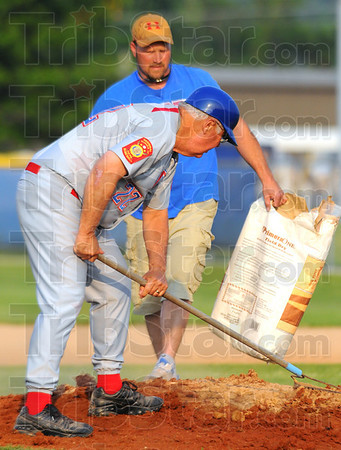 Tribune-Star/Jim Avelis<br /> Drying out: Post 346 manager John Hayes rakes drying agent into the pitchers mound with help from David Sexton.