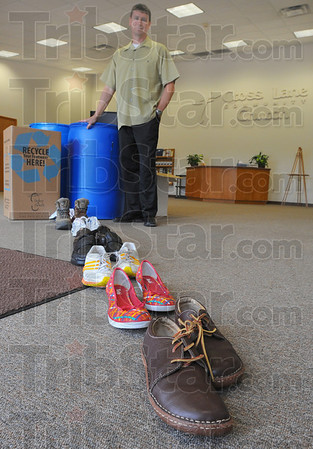 """Tribune-Star/Jim Avelis<br /> Sole man: Cross Lane Churchs' Tracy Sutliff stands by the containers he hopes will be filled on """"Barefoot Sunday"""". The church is participating in Soles4Souls which distributes new and gently worn shoes to those in need around the world."""