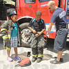 Tribune-Star/Rachel Keyes<br /> Suit up: Seven-year-old Nevaeh Moore (left) watches brother Rramas Moore (middle) as Sugar Creek firefighter Ted York helps him put on fire gear.