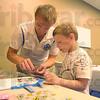 Tribune-Star/Rachel Keyes<br /> Making it fly: Indiana State Student Josh Loudermild (left) helps six-year-old John Lawson III make a airplane.