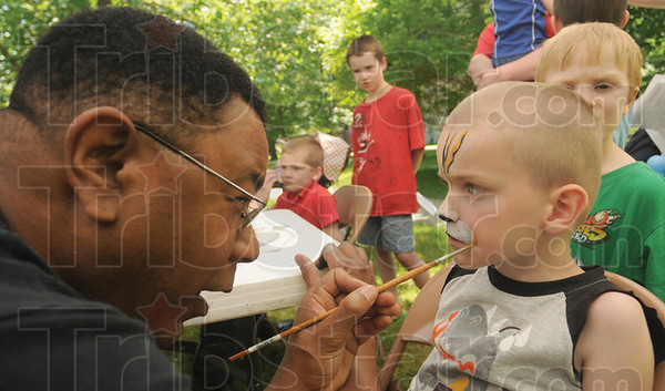Tribune-Star/Rachel Keyes<br /> Eye of the tiger: Volunteer Edward Holloman (left) paints a tiger face on five-year-old Tyler Duncan at the Sister's of Providence Family Day.