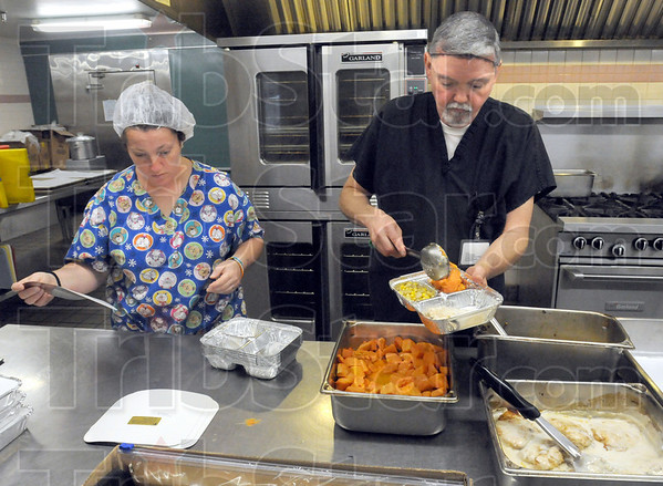 Meals on wheels: Royal Oaks assistant cook Dottie Tighe and cook supervisor Bernie Stevenson prepare hot meals for the delivery program Friday morning.