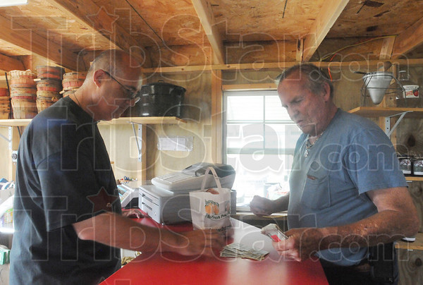 Tribune-Star/Rachel Keyes<br /> Keeping it alive: Dallas May (left) sells peaches to customer Thomas Woods (right) Saturday at Swanee Orchards. Dallas has been running the family Orchard since 1993.