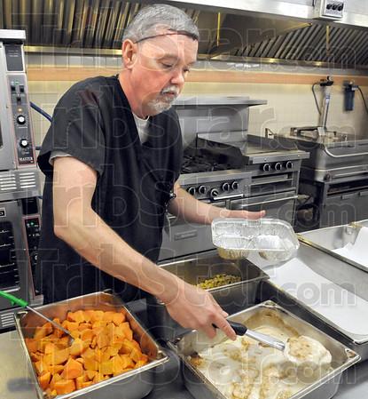 Meal maker: Bernie Stevenson, cook supervisor at Royal Oaks prepares a hot meal for Meals on Wheels recipients Friday morning.