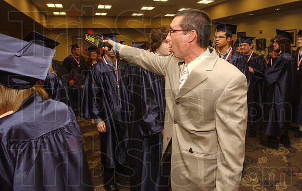 Tribune-Star/Jim Avelis<br /> On point: Terre Haute North High School Dean of Students Michael Menser creates order from chaos in lining his students up in proper order for their graduation Sunday afternoon.