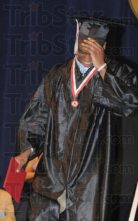 Tribune-Star/Rachel Keyes<br /> Thanks guys: Terre Haute South's Antoine Burks hides his head as his family and friends holler in the stands as his name is called to receive his diploma.
