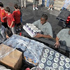 Volunteers: A group of volunteers load two trucks with palets of canned foods Friday morning at Baesler's Market.