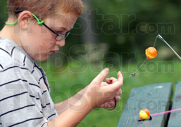 Bait: Ten-year-old Donnie Olson baits his hook as he participates in the annual Fishing Rodeo Saturday morning.